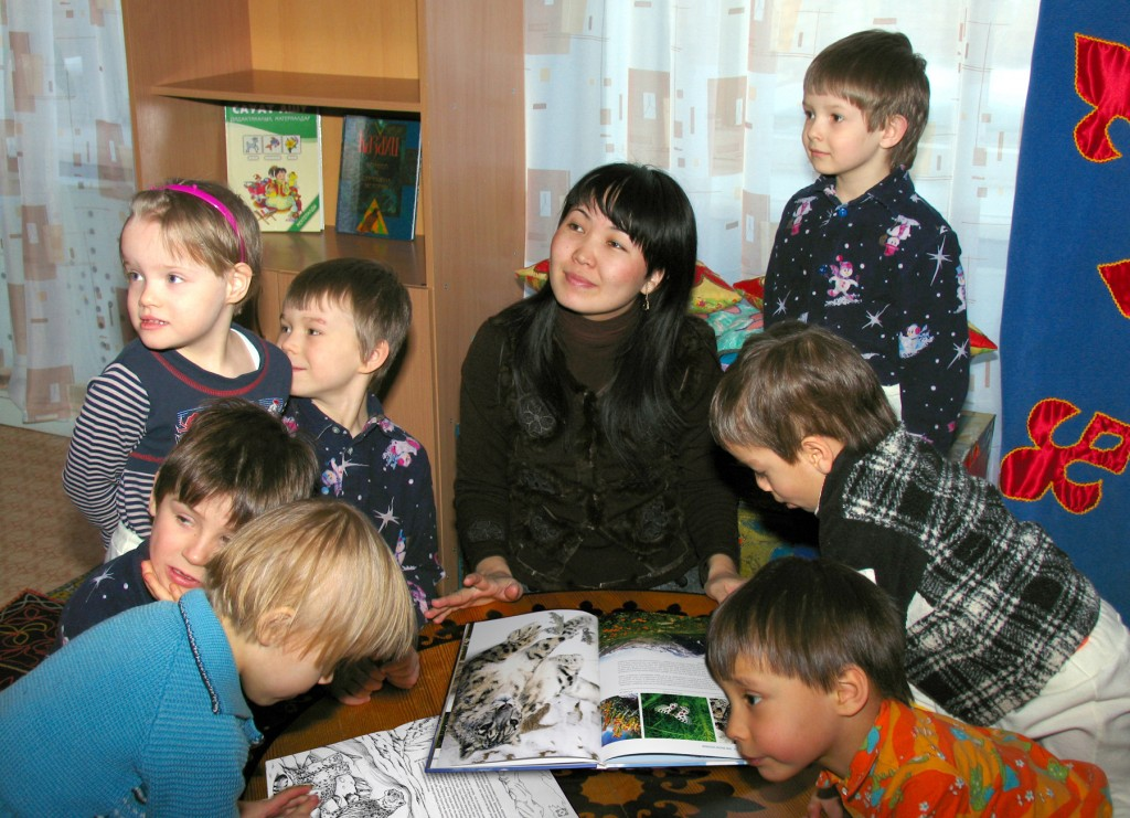 children looking at snow leopard book that a woman is holding