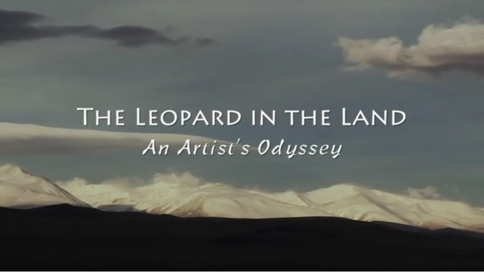 """Words: """"The Leopard in the Land An Artist's Odyssey across a landscape with mountains in the background"""